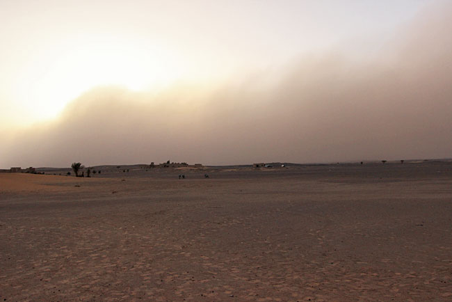 A sandstorm in the Sahara Desert in Morocco flows over the distant hills as we drive to our tent camp
