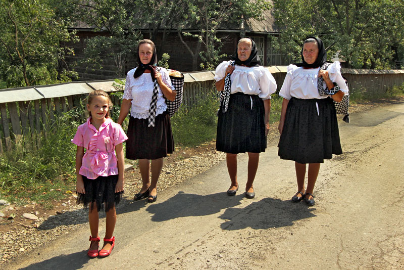 Women Wear Traditional Dress in Breb, Romania is a Wide Black Skirt, White Ruffled Blouse, and Headscarf