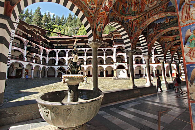 Looking through fresco-painted colonnades of the Nativity of the Virgin Church to arches set upon stone columns that form the loggias of the monastic apartments at Rila Monastery