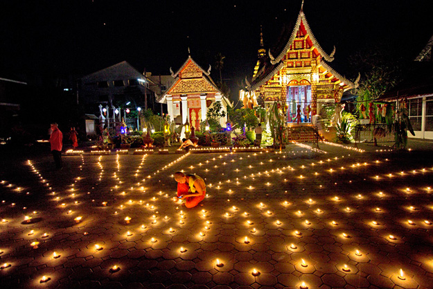 Monks tend to candles placed in a starburst pattern in the courtyard of Wat Muentoom during Yi Peng Festival in Chiang Mai