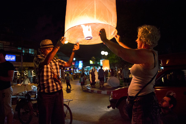 Tourists join in the fun of Yi Peng by lighting and sending aloft a lantern