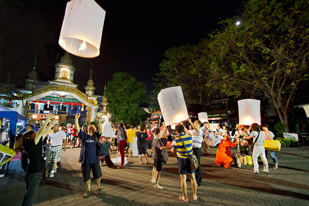 The grounds of Wat Umokot are filled with festival-goers sending paper lanterns into the night sky