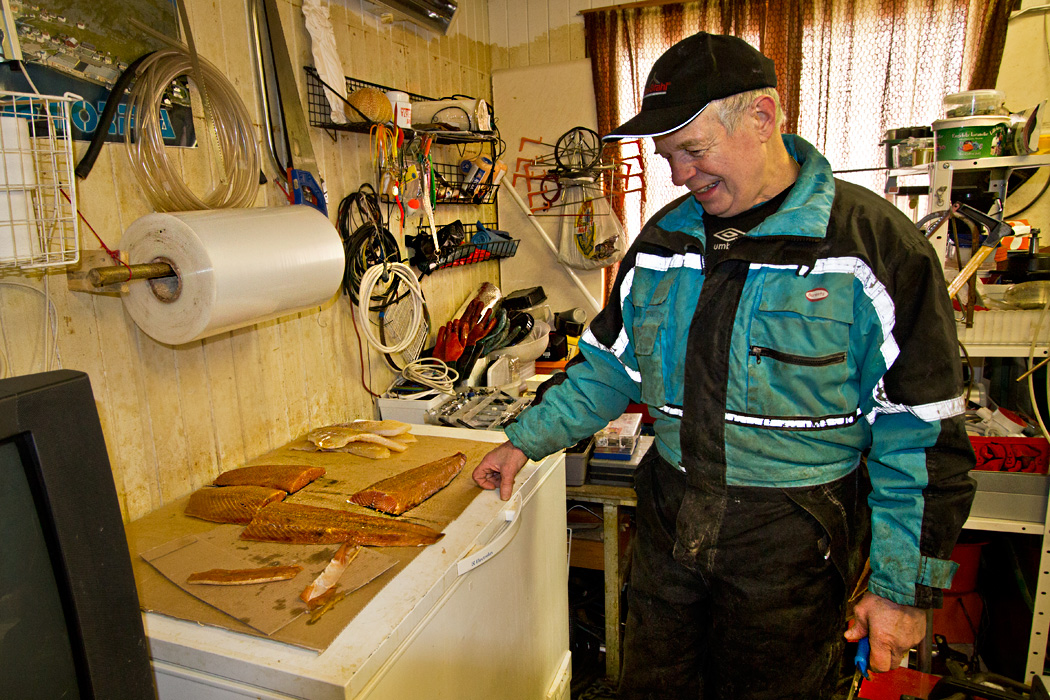 Alfred, a fisherman in the town of Honningsvag Norway, offers me fresh smoked salmon in his shop on the harbor