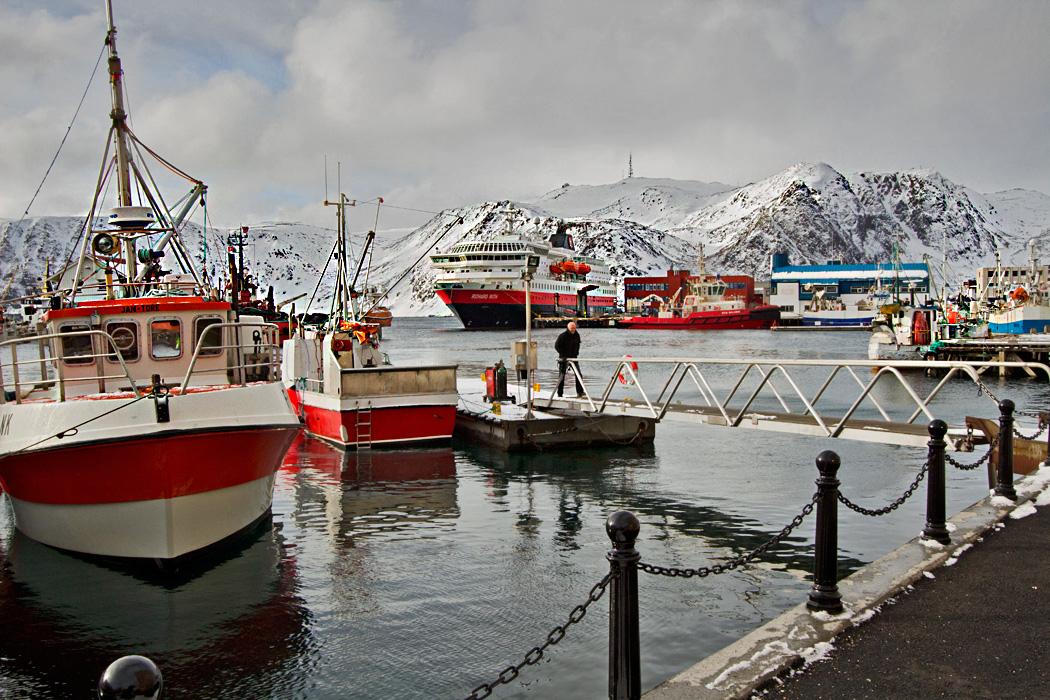 In the white landscape of Honningsvag Norway, boats in the harbor provide a welcome splash of color