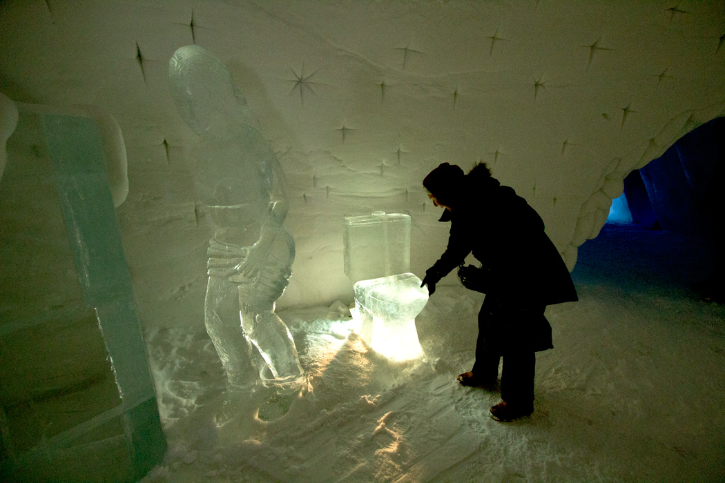 Visitor to the Snow Hotel in Kirkenes Norway tries to lift the lid of a toilet sculpted of ice