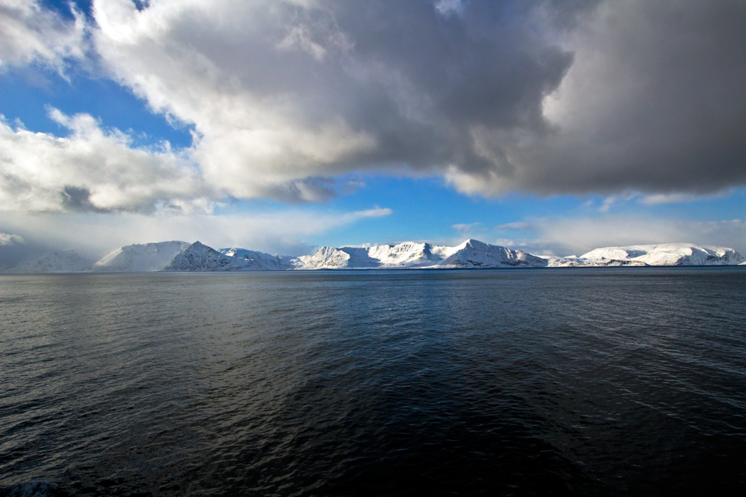 Ultramarine seas and snow-dusted rocks, stunning scenery above the Arctic Circle, near Hammerfest, Norway
