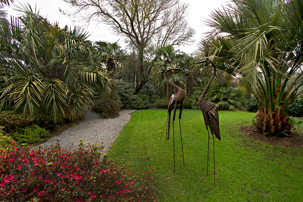 Bronze flamingos grace a lush expanse of lawn at Lamorran House Gardens in Cornwall, England