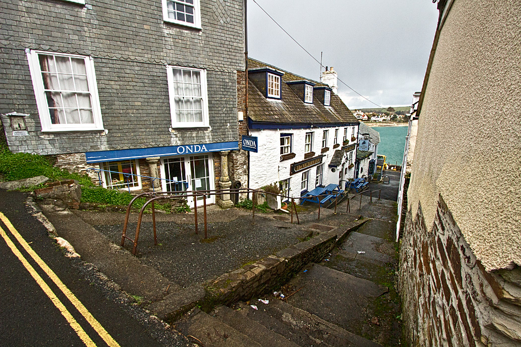 A stairway down to the sea and the shops along the bay in Saint Mawes, Cornwall, England