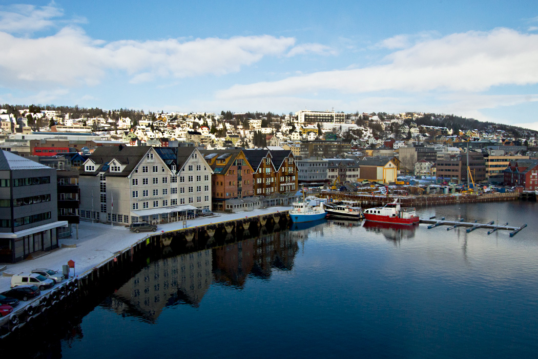 Prim buildings are mirrored in the in glassy waters of the harborfront in Tromso, Norway