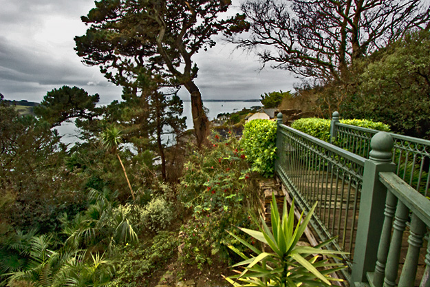 Bridge over a mini-canyon at Lamorran House Gardens, with view to Falmouth Bay