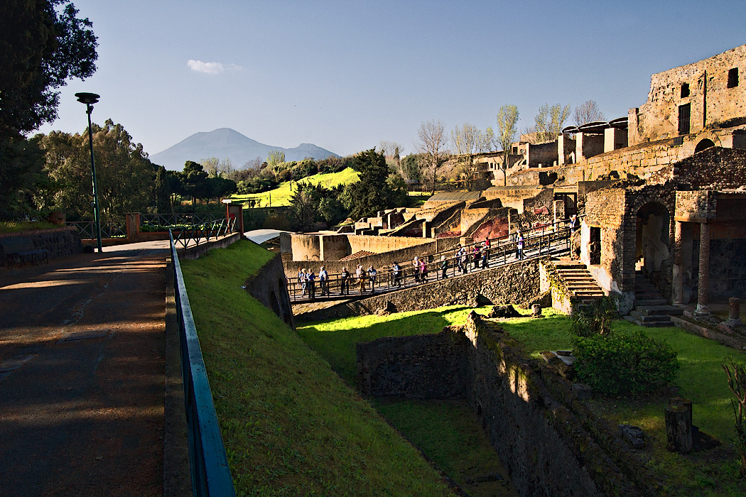 View of the entrance to the ruins of Pompeii, Italy, with unexcavated hills and Mount Vesuvius in the background