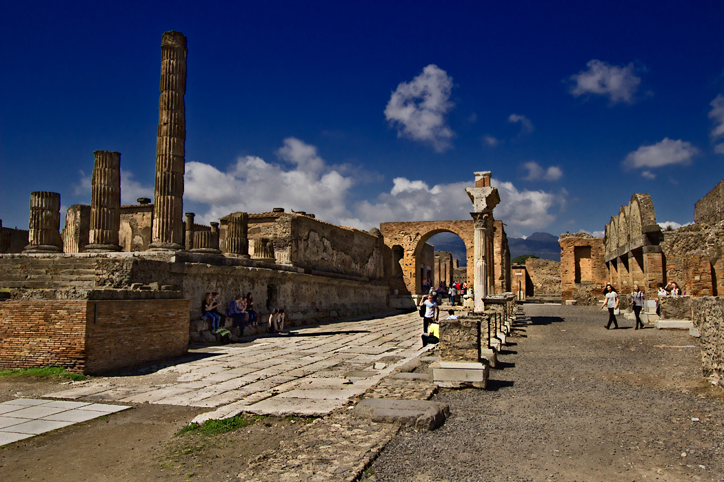 Temple of Jupiter and honorary arch form one end of the Forum in Pompeii. Lurking in the background is Mount Vesuvius, with its blown-off top, which erupted in 79 AD and buried the town in ash