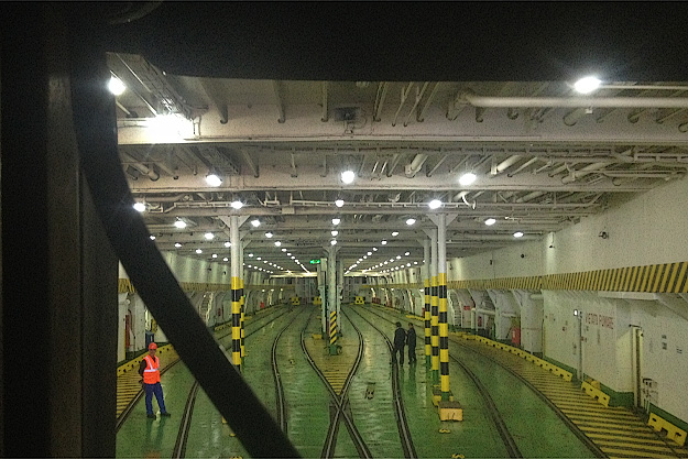 Train cars roll into the bowels of the ferry boat