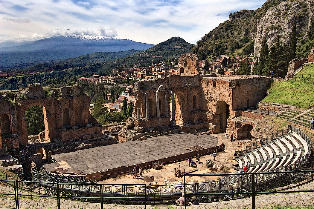 Greek Amphitheater in Taormina, Sicily, with snow-capped Mount Etna in the distance