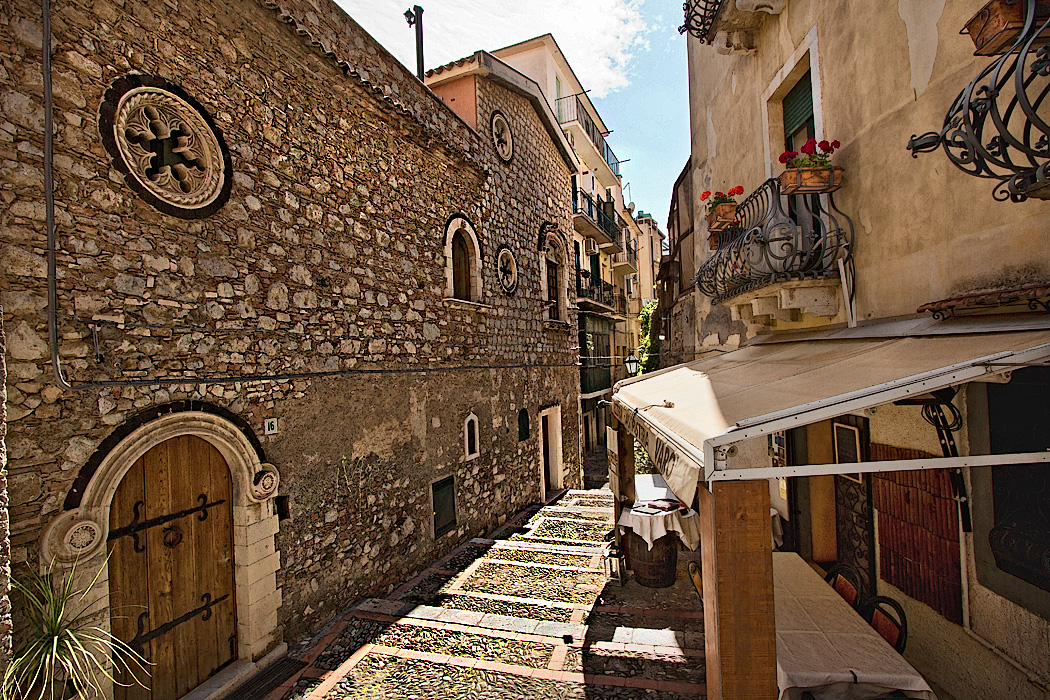 Typical street in Taormina, Sicily is paved with cobblestones and lined with lovingly restored buidlings