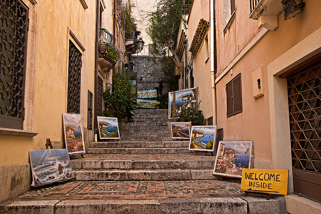 Artist in Taormina, Sicily, lures customers into his shop at the top of the stairway with displays of his work