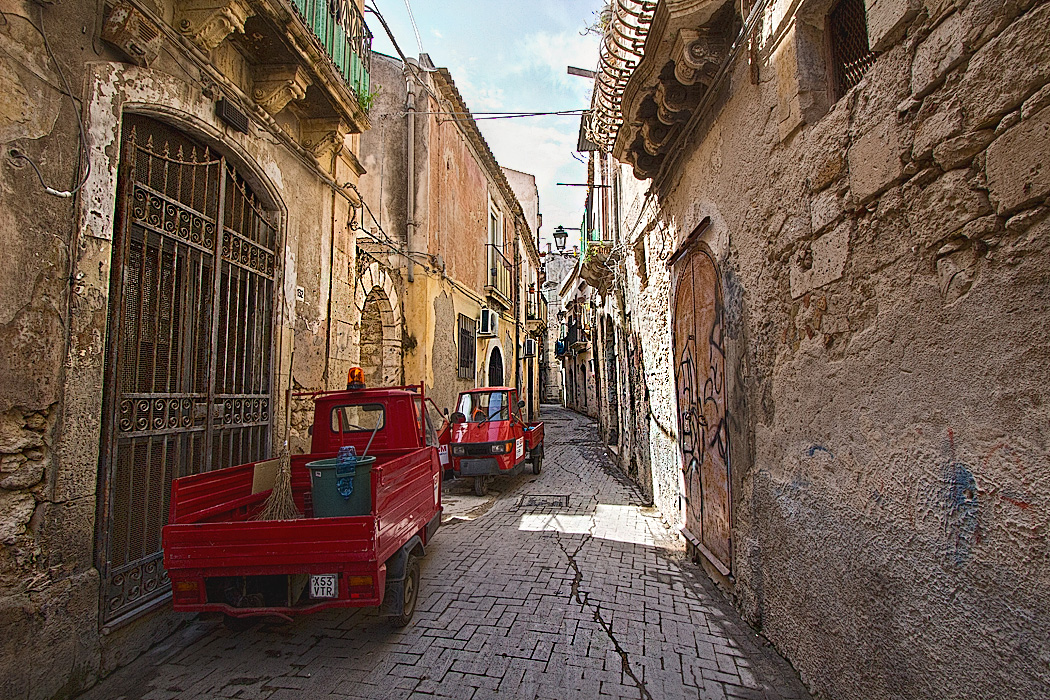 Miniature red three-wheel trucks are used extensively on Ortigia Island, the Old Town area in Syracuse, Sicily, as they are perfectly sized for the ancient cobblestone streets.