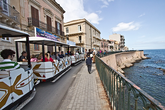 Tourist train carries people around the Old Town of Syracsue, Sicily