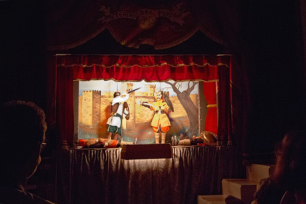 Puppets with shield and sword mount a fierce battle during a performance at Teatro dei Pupi