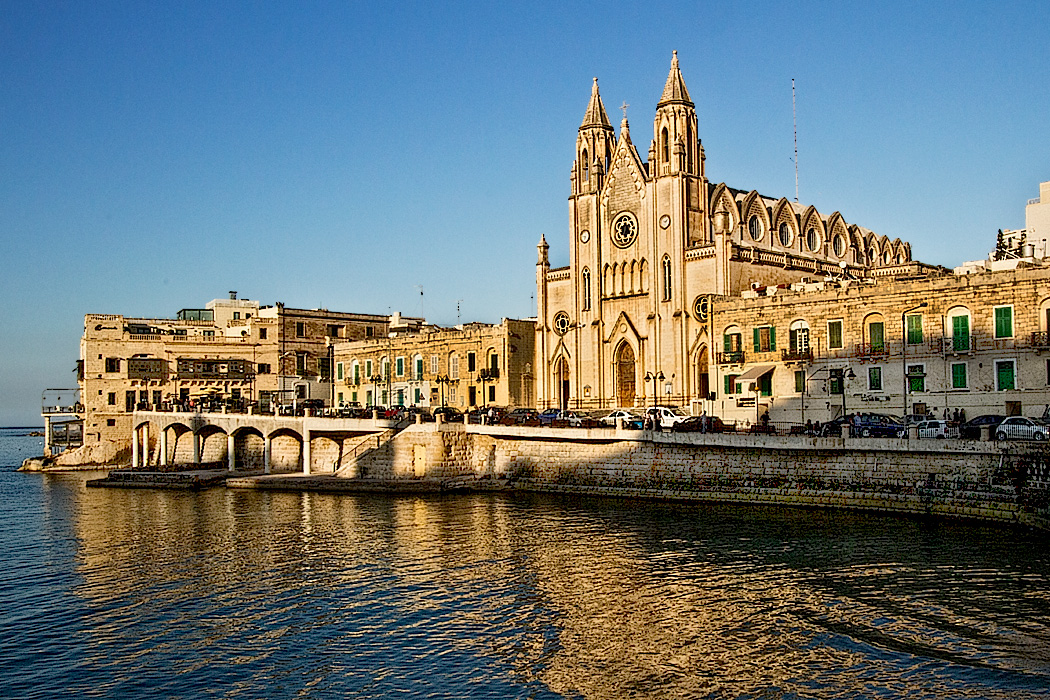 Our Lady of Mount Carmel Church is bathed in golden light from the setting sun on Baluta Bay in St. Julian's, Malta