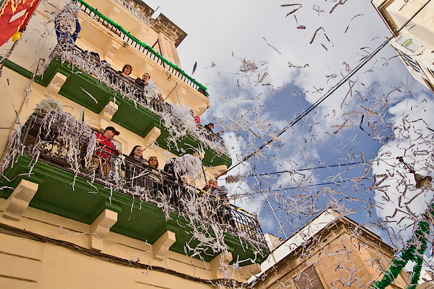 Residents of Floriana throw confetti down on parade participants during the Feast of St. Publius