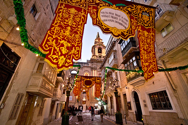 Streets with enormous tapestries and illuminated church steeple at the St. Publius feast day winds down