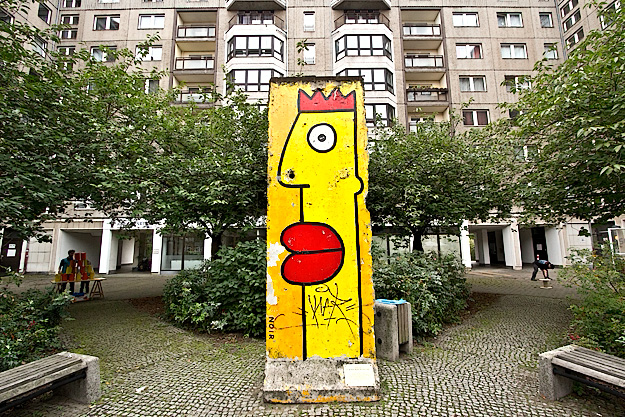A small section of the Berlin Wall stands in the courtyard of a spartan apartment building in Berlin