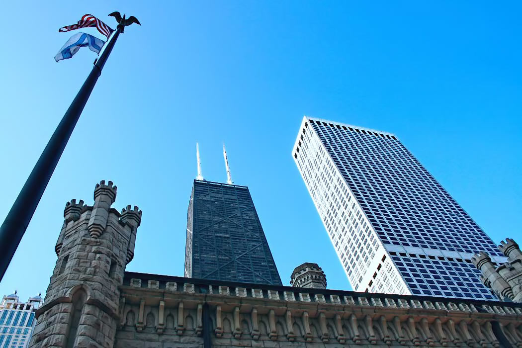 Hancock Tower, with its distinctive zig-zag black facade and twin white towers, looms over the crenelated towers of Chicago's Water Tower