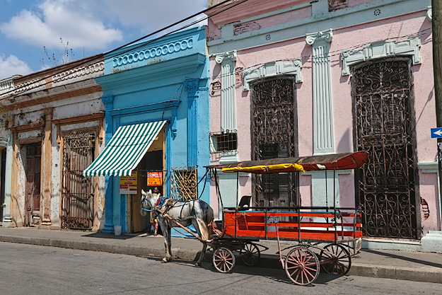 Horse-drawn carriage on the streets of Santa Clara. Travel to Cuba before scenes like this begin to disappear.
