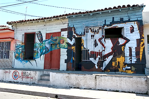 Murals on the houses in neighborhood surrounding Trazos Libres community art project in Cienfuegos, Cuba