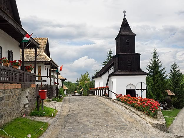 Main street in the historic center of Holloko leads past adobe houses with stone foundations, to the wooden-steepled church