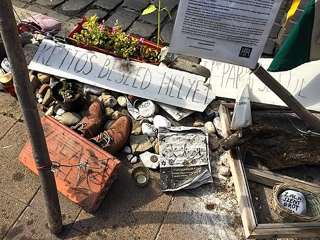 Detail of some of the items that have been left in front of the memorial by holocaust survivors, descendants, and concerned citizens