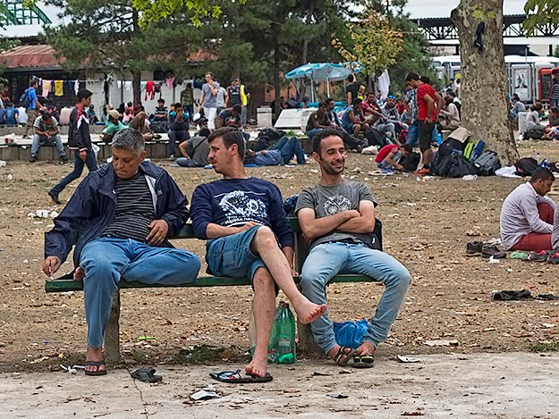 Syrian refugees in Serbia chat on a bench in a park near the bus station as they await their chance to move deeper into Europe