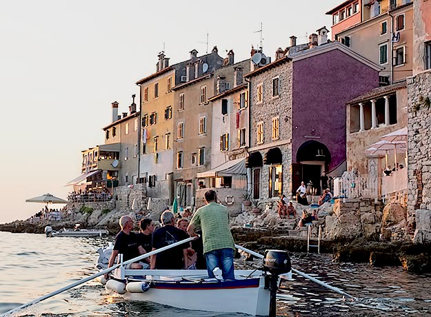 The setting sun gilds window frames of waterfront houses in Rovinj as the batanas make their way around the pier