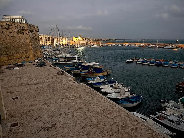 Sun sets over the marina on the Ionian Sea in Gallipoli, Italy
