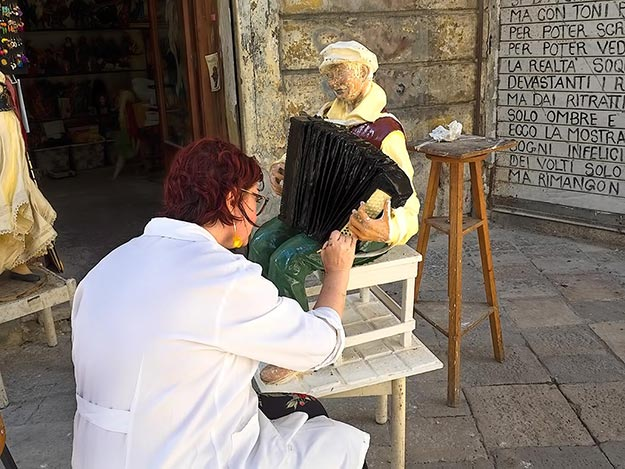Artist paints details on a papier mache sculpture on the streets of Lecce, Italy