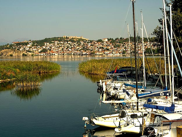 One of the rivers that spill into Lake Ohrid provides the perfect harbor for sailboats. The hilltop town of Ohrid is seen in the distance, with its old stone fortress atop the hill.