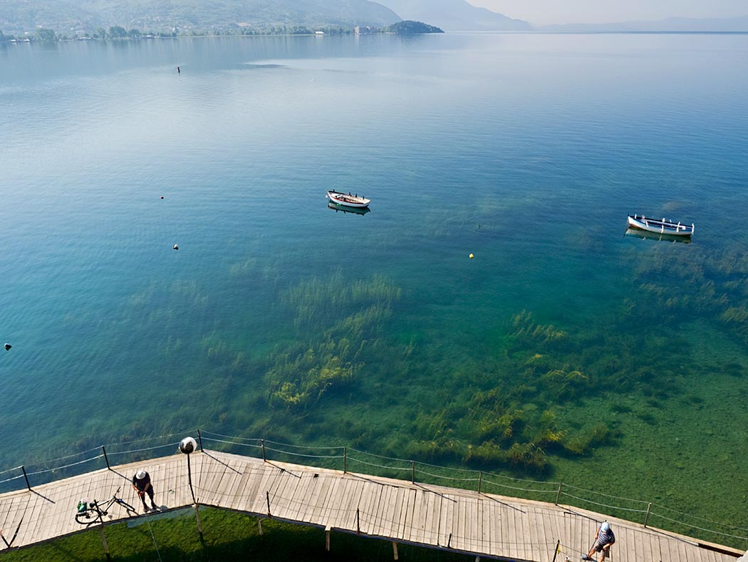 Fishermen cast lines from a wooden boardwalk that follows the cliffs surrounding Ohrid Lake in Macedonia