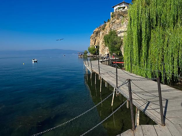 A wooden boardwalk leads around the cliff faces to pocket beaches and cafes where locals and guests tarry for hours