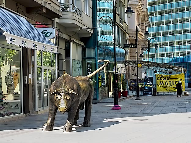 Brass bull in Skopje stands in front of a shoe store