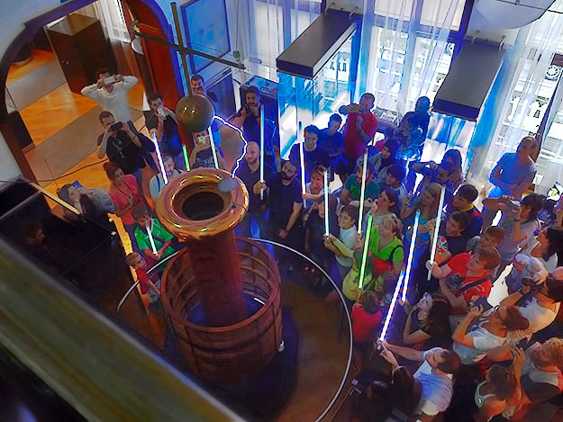 View from above as the Tesla Coil is turned on and electricity flows through the air, lighting up the flourescent tubes held by visitors