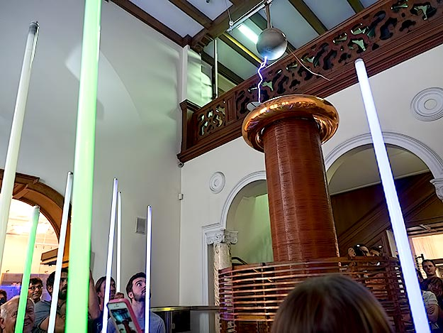 Flourescent tubes held by visitors at the Nikola Tesla Museum, with no wires connected to anything, light up when Tesla Coil is turned on