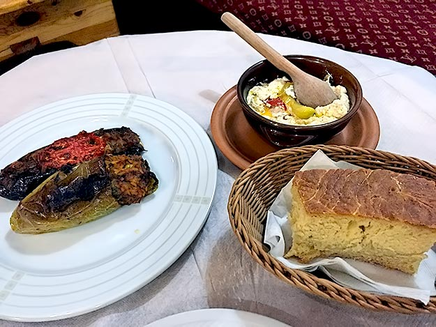 My traditional Albanian meal: peppers stuffed with rice and garlic, roasted eggplant stuffed with onions and tomatoes, soft baked sheep cheese with peppers, and homemade bread