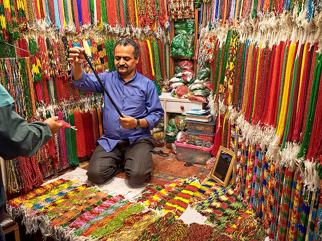 Shop owner strings a custom necklace in the Pote Bazaar (bead market) area of Indra Chowk in Kathmandu, Nepal