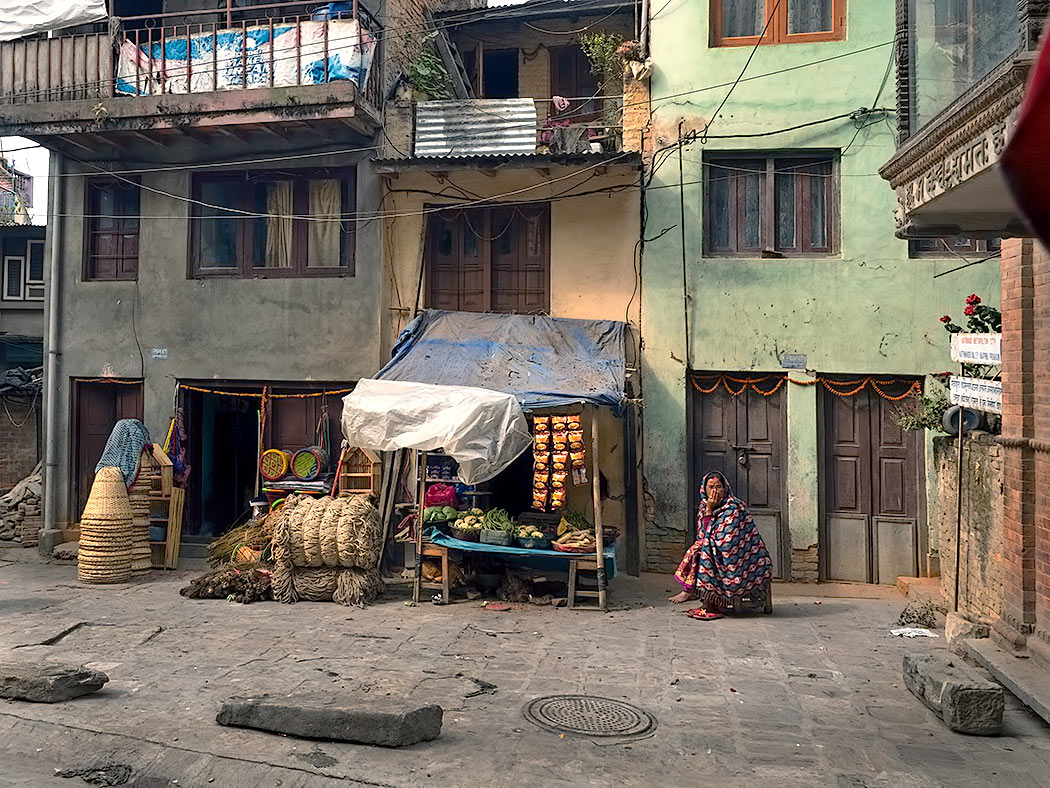 Nepali woman squats next to her makeshift vegetable stand in Kathmandu, Nepal