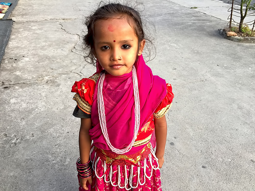 Girl with kohl-ringed eyes and a red tika on her forehead is all dressed up and waiting to perform the Bhailo dance during the Hindu holiday of Tihar in Pokhara, Nepal