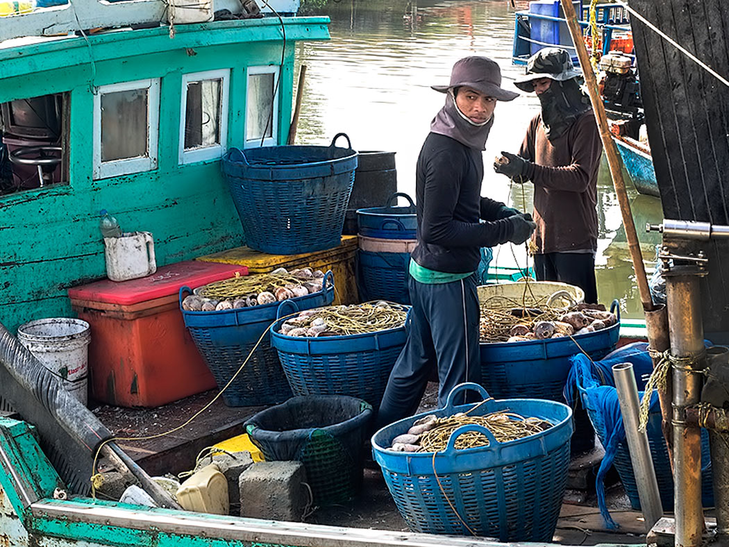 Fishermen at Khao Takiab clean and prepare float lines after returning with the morning's catch in Hua Hin, Thailand
