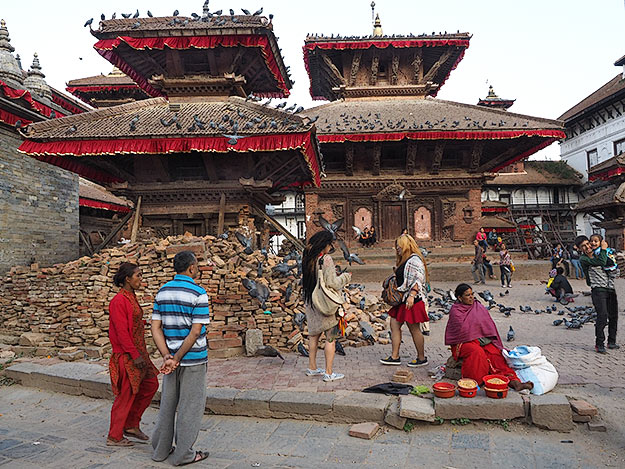 Kathmandu's Durbar Square, where life in Nepal afer the earthquake goes on as usual. This woman still sells corn kernels to fee the ubiquitous pieons that flood the old palace grounds.