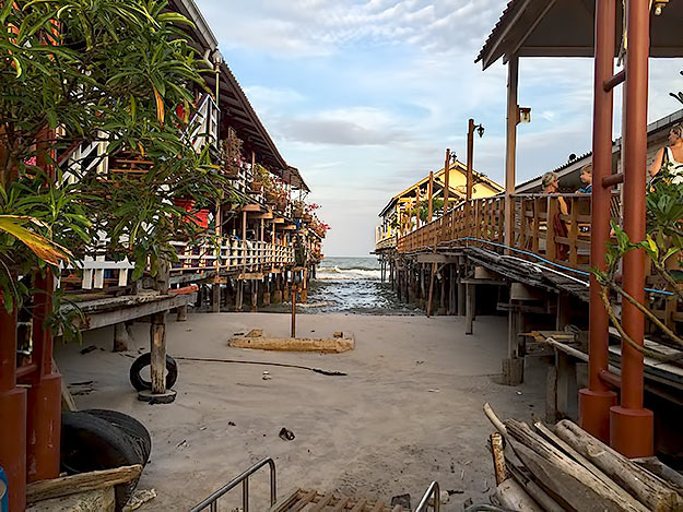 Seafood restaurants perch on long wooden wharves built over the Gulf of Thailand