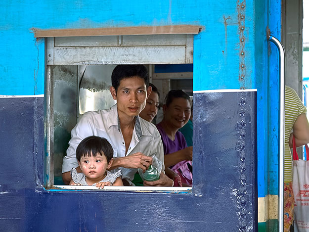 Father and daughter look out through the window of a carriage on the Circular Train in Yangon